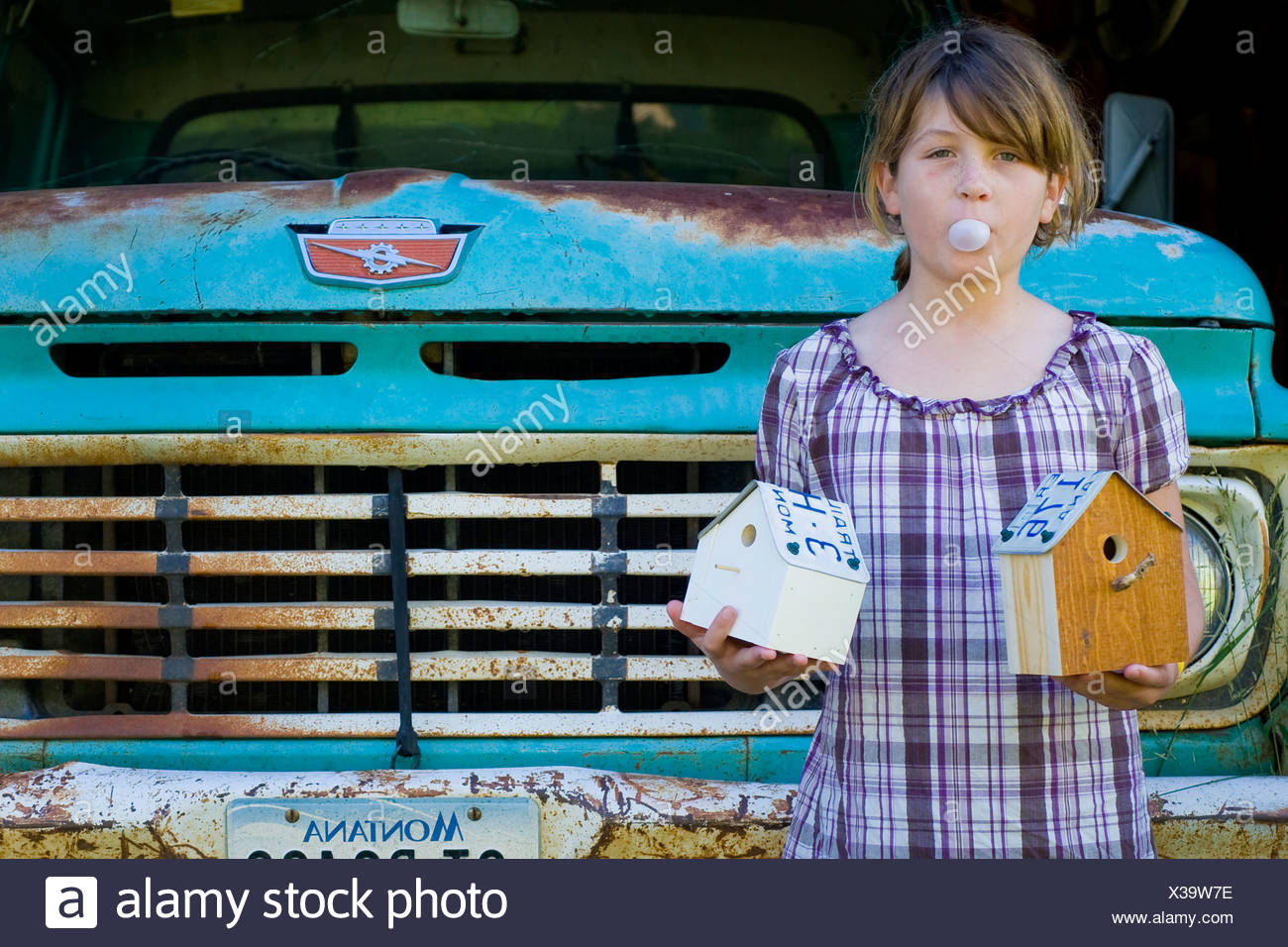 Girl Blowing Bubble Gum And Holding Birdhouses In Front Of A Rusty Pick Up  Truck