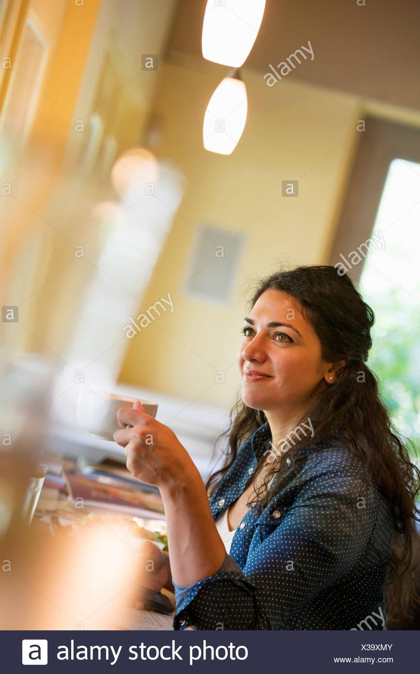 A woman having a cup of coffee. - Stock Image