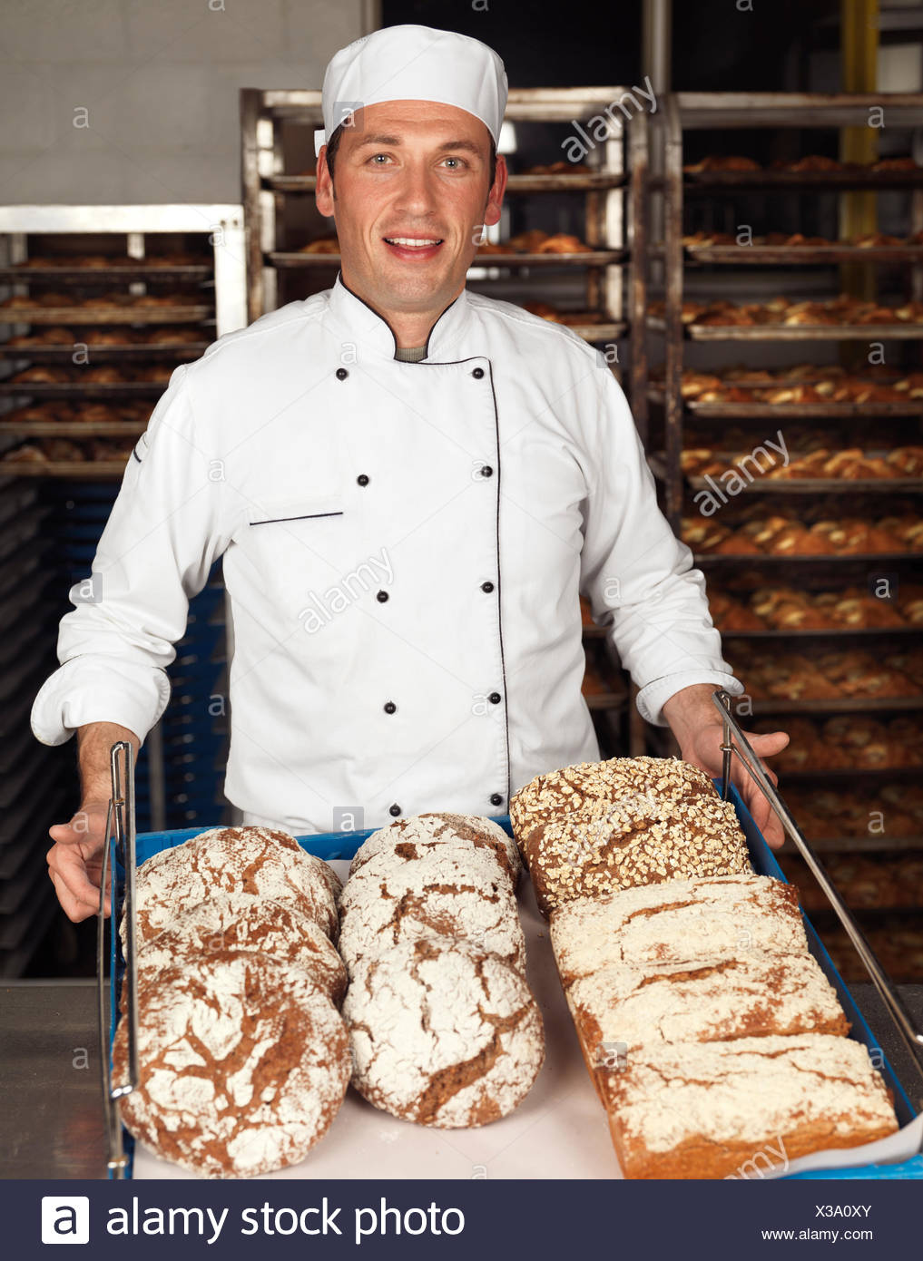 Baker holding a tray with freshly baked bread loaves in a bakery - Stock Image