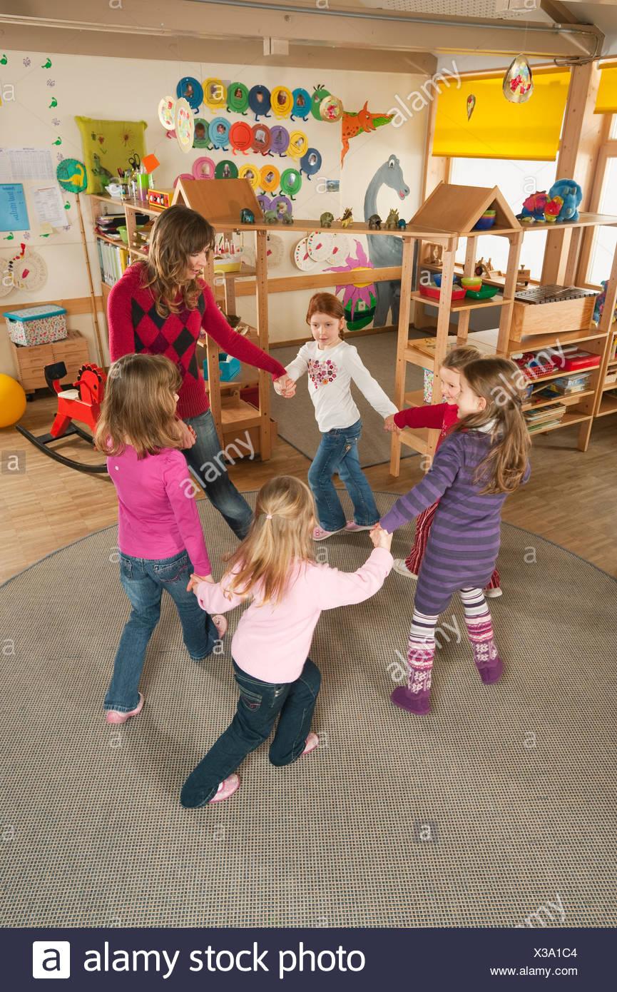 Germany, Nursery, Female nursery teacher and children dancing - Stock Image