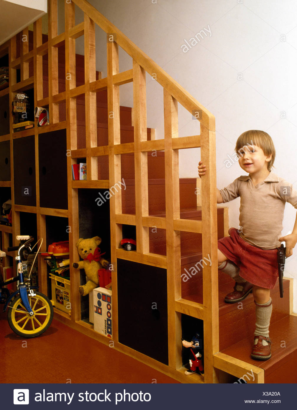 Small Boy Standing On Staircase With Under Stair Storage In A Seventies Hall Stock Photo Alamy