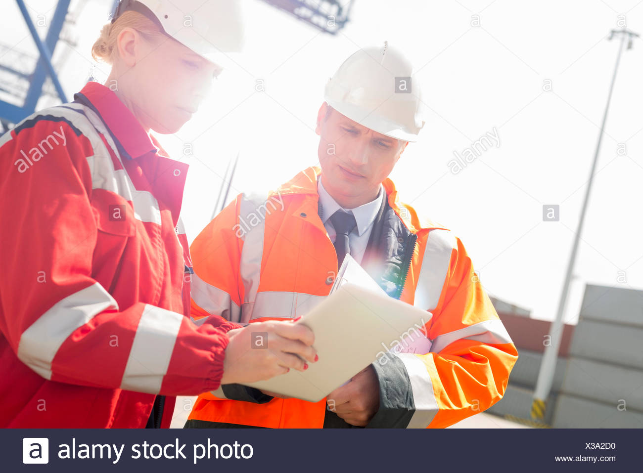 Workers discussing over tablet computer in shipping yard - Stock Image
