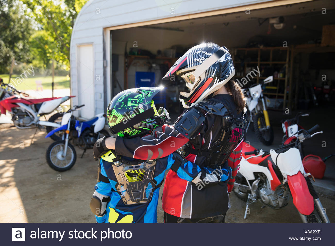 Mother and daughter in motorbike helmets hugging in sunny driveway - Stock Image