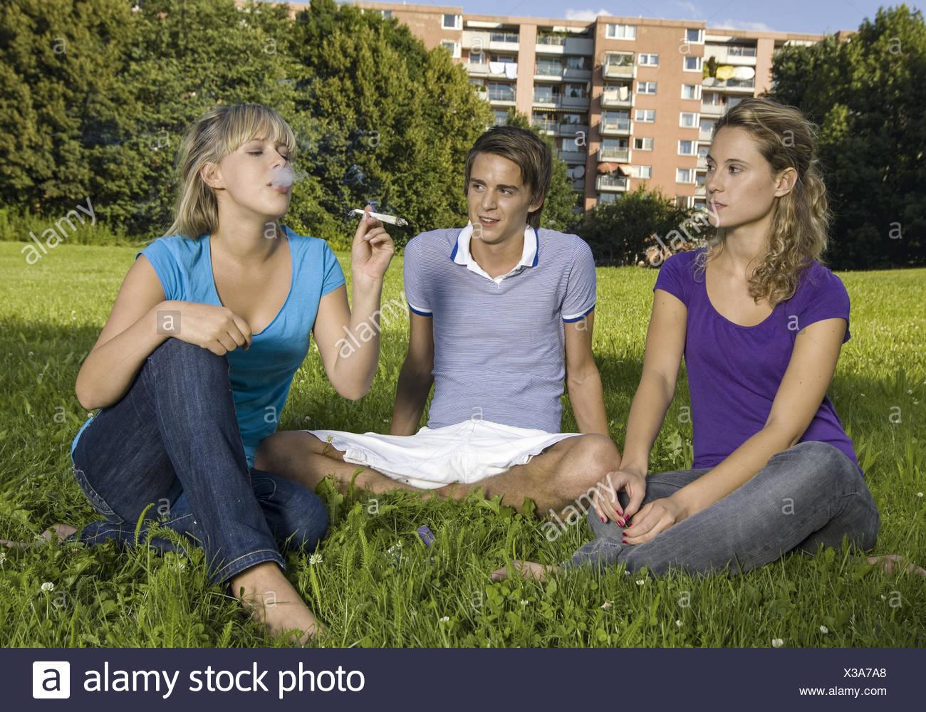 Drei Teenager sitzen auf Wiese, rauchen Joint (model-released) - Stock Image