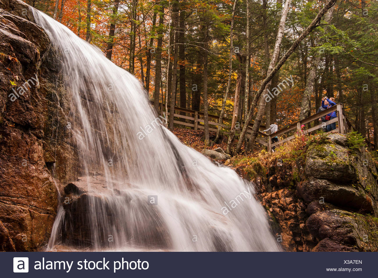 Tourists observing a scenic water fall at Flume Gorge. - Stock Image