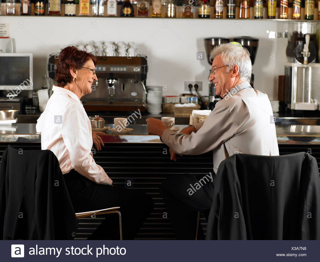 Businesspeople at a bar drinking coffee. - Stock Image