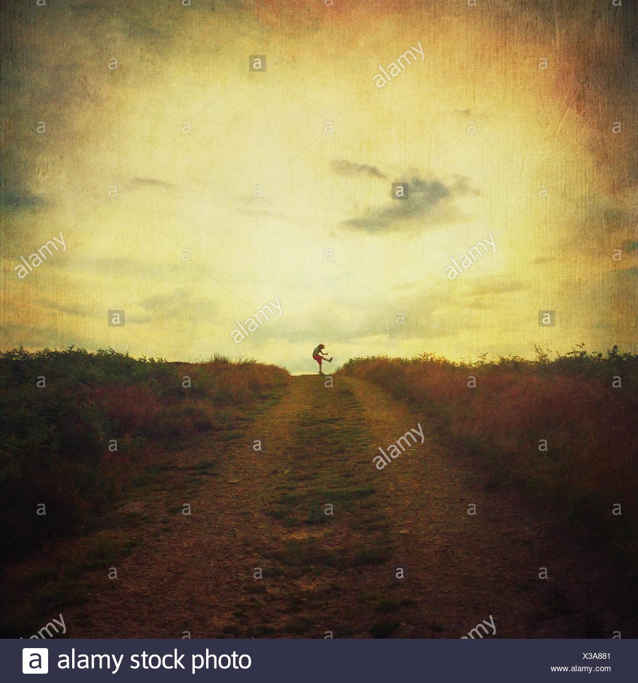 Distant View Of Person Jumping On Dirt Road Against Sky - Stock Image