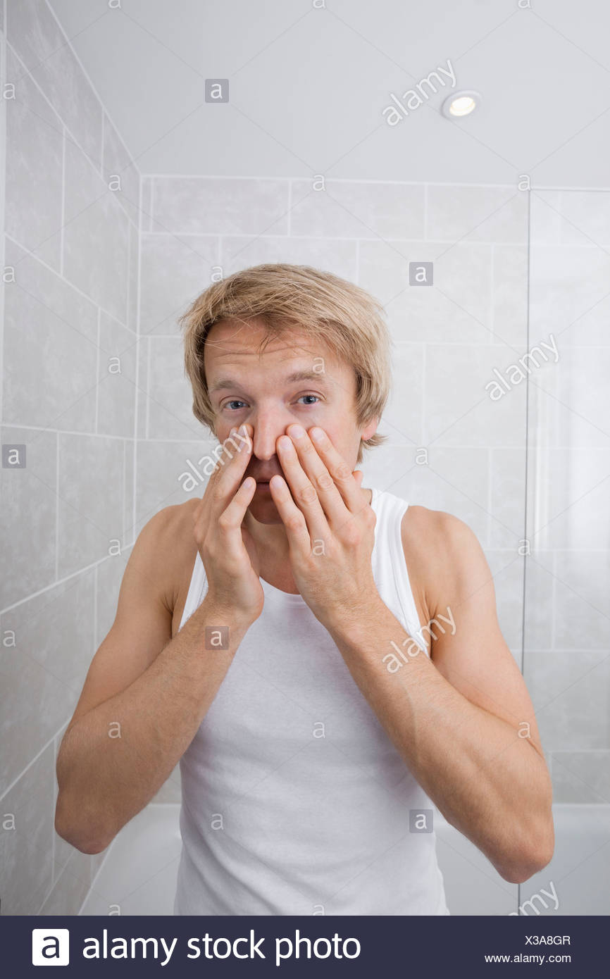 Portrait of man checking for wrinkles on his face in bathroom - Stock Image
