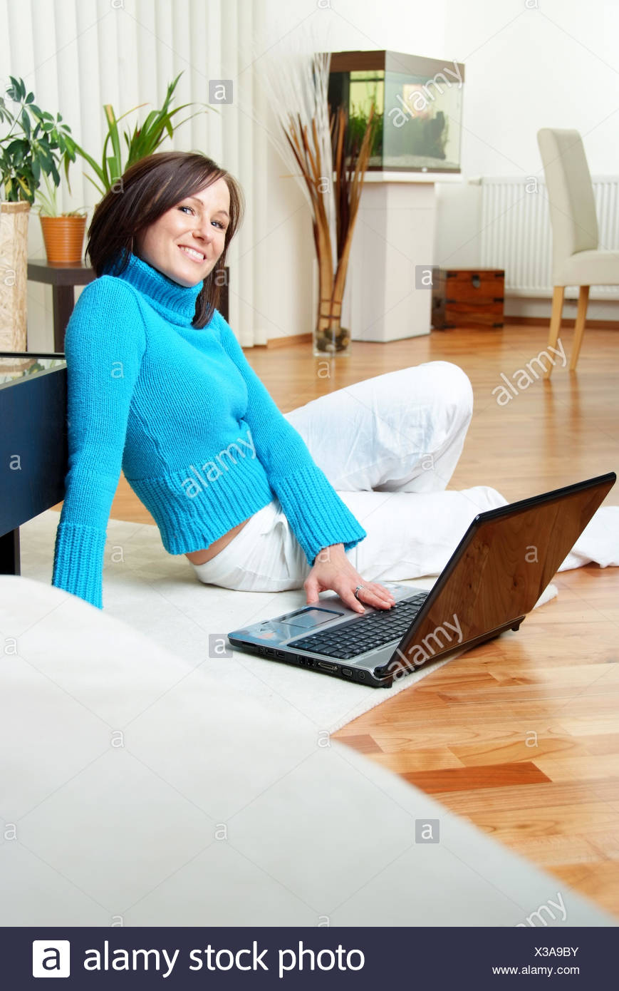 Young woman at home using laptop - Stock Image