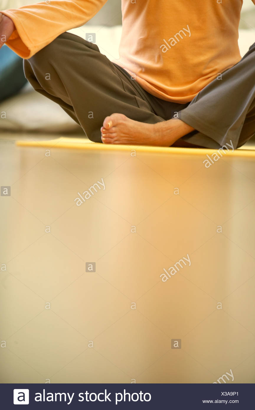 A woman sitting crossed legged on a yoga mat, close-up - Stock Image