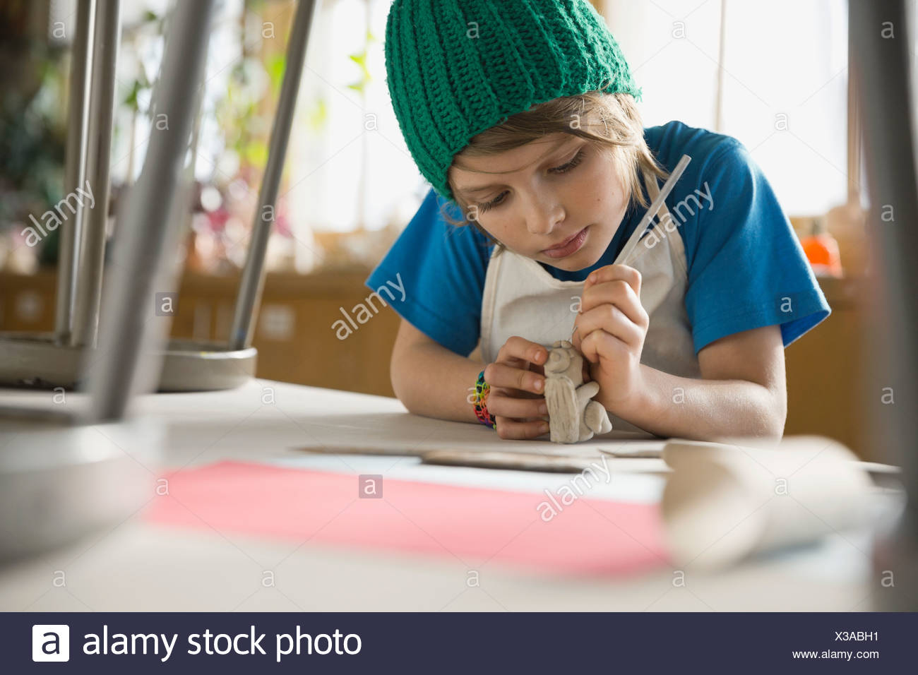 Boy making clay figurine in art class Stock Photo