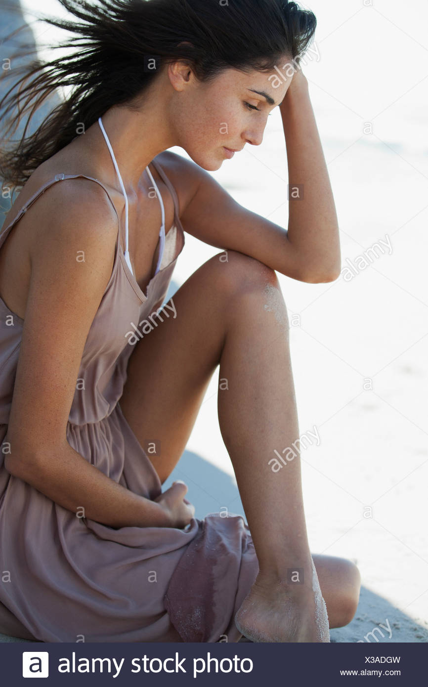 Pensive woman with head in hands - Stock Image