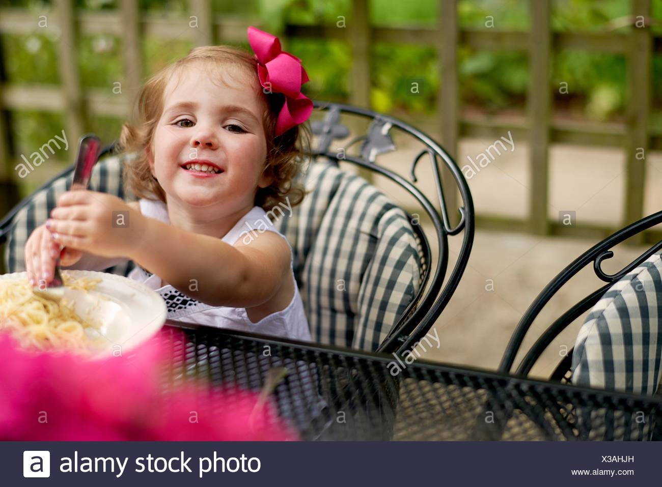 Girl dining at garden table looking at camera smiling - Stock Image
