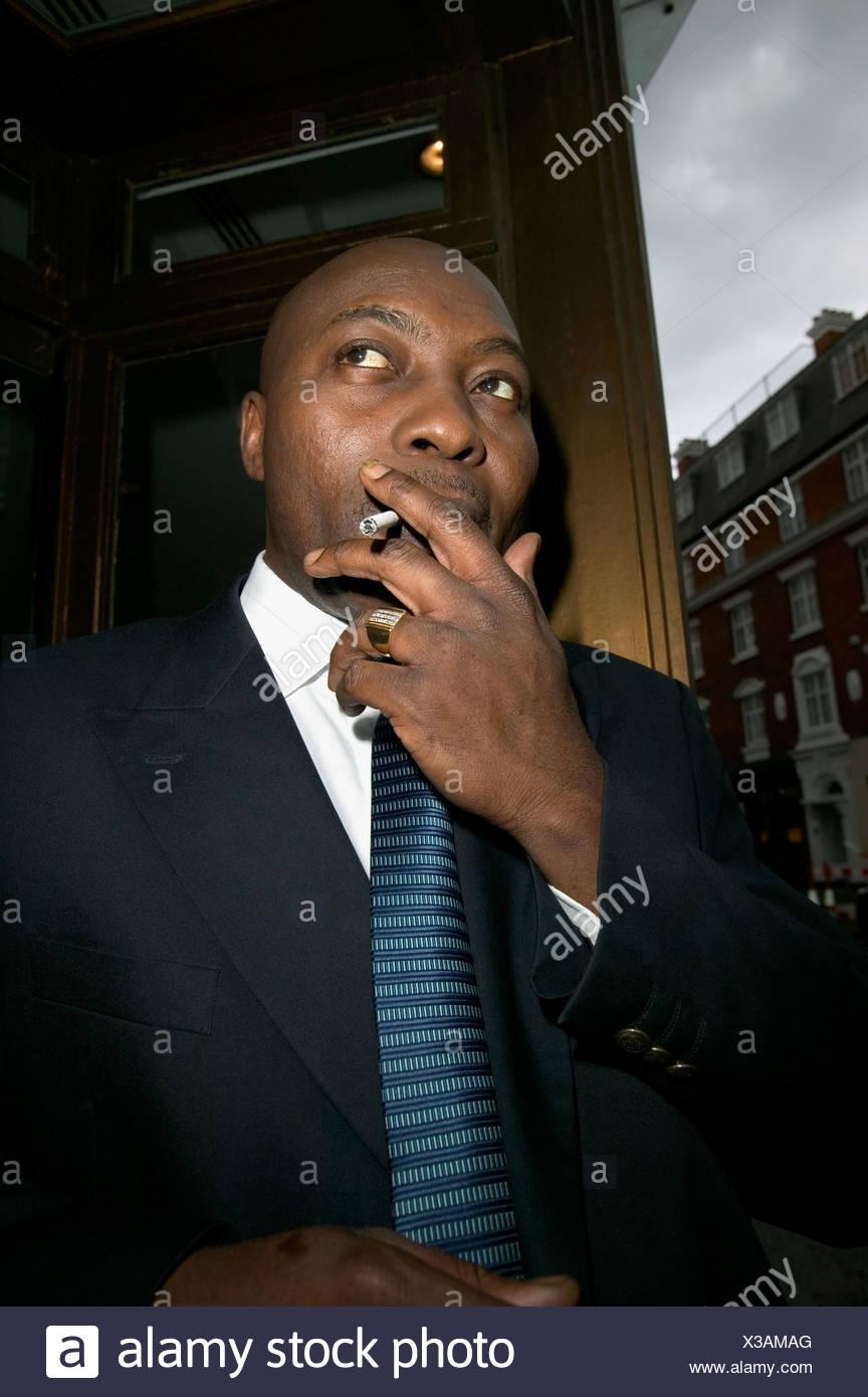 Businessman smoking a cigarette - Stock Image