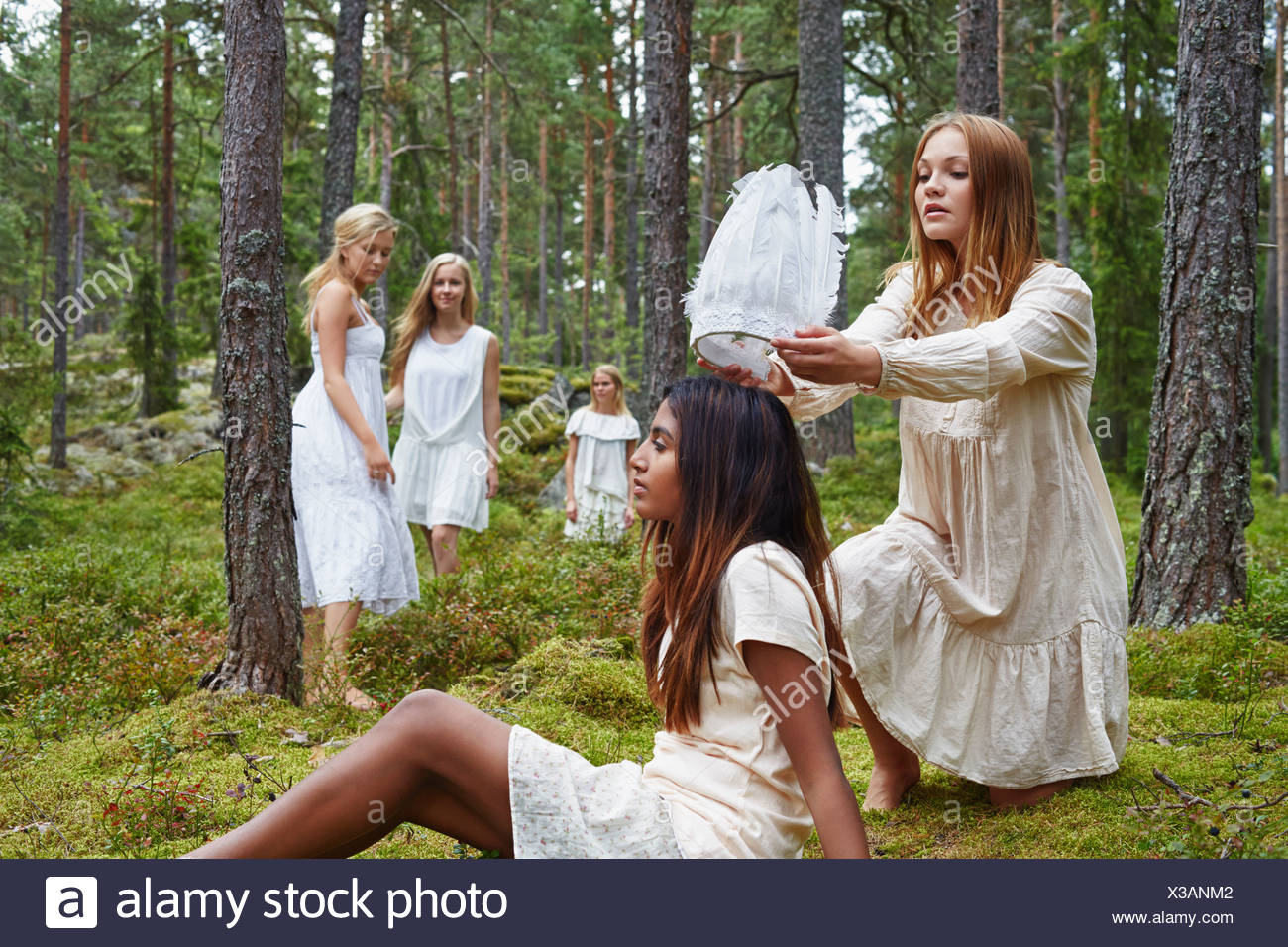 Teenage girl putting white hat on friend in forest - Stock Image