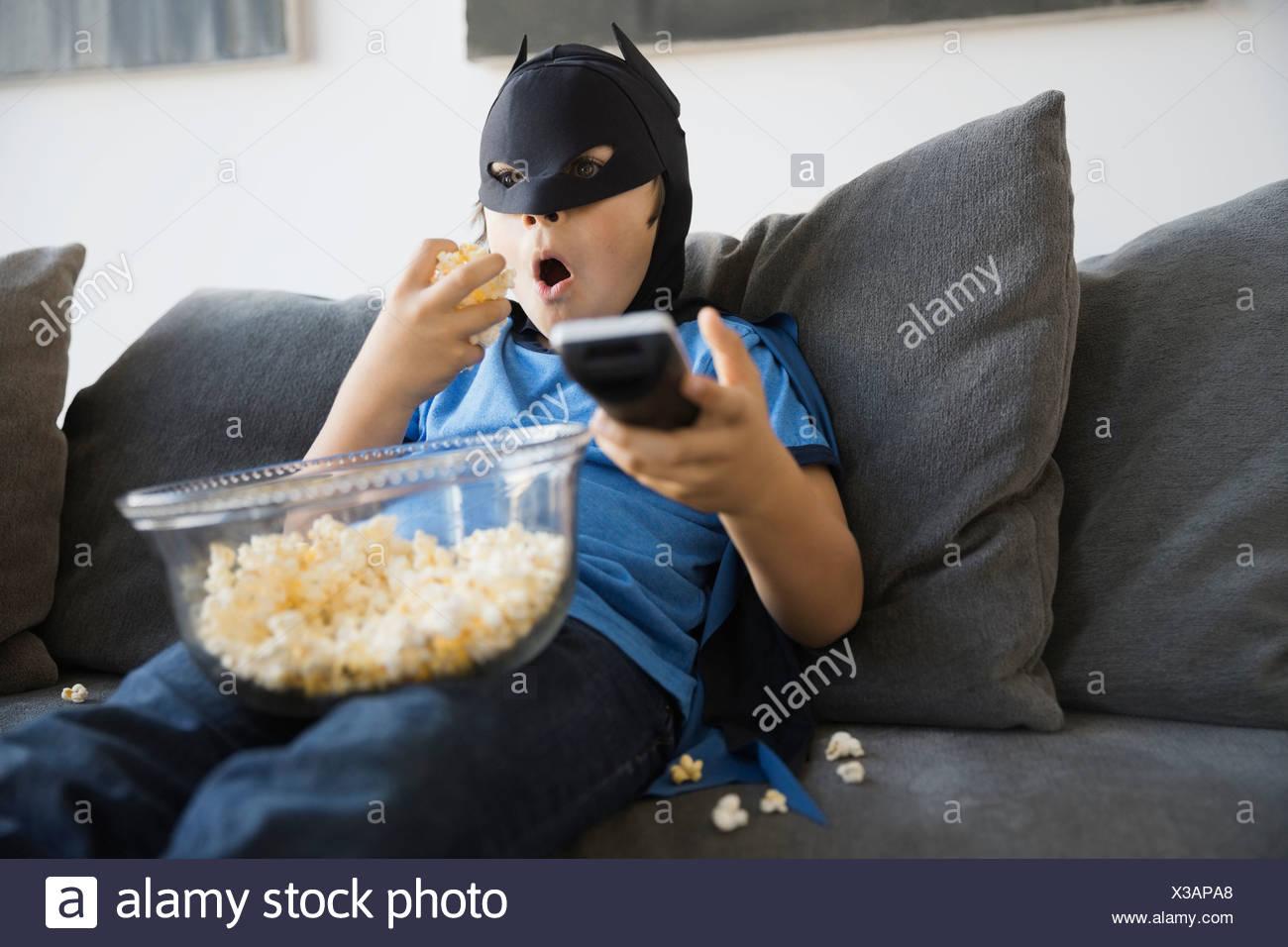 Boy in superhero costume watching TV at home - Stock Image