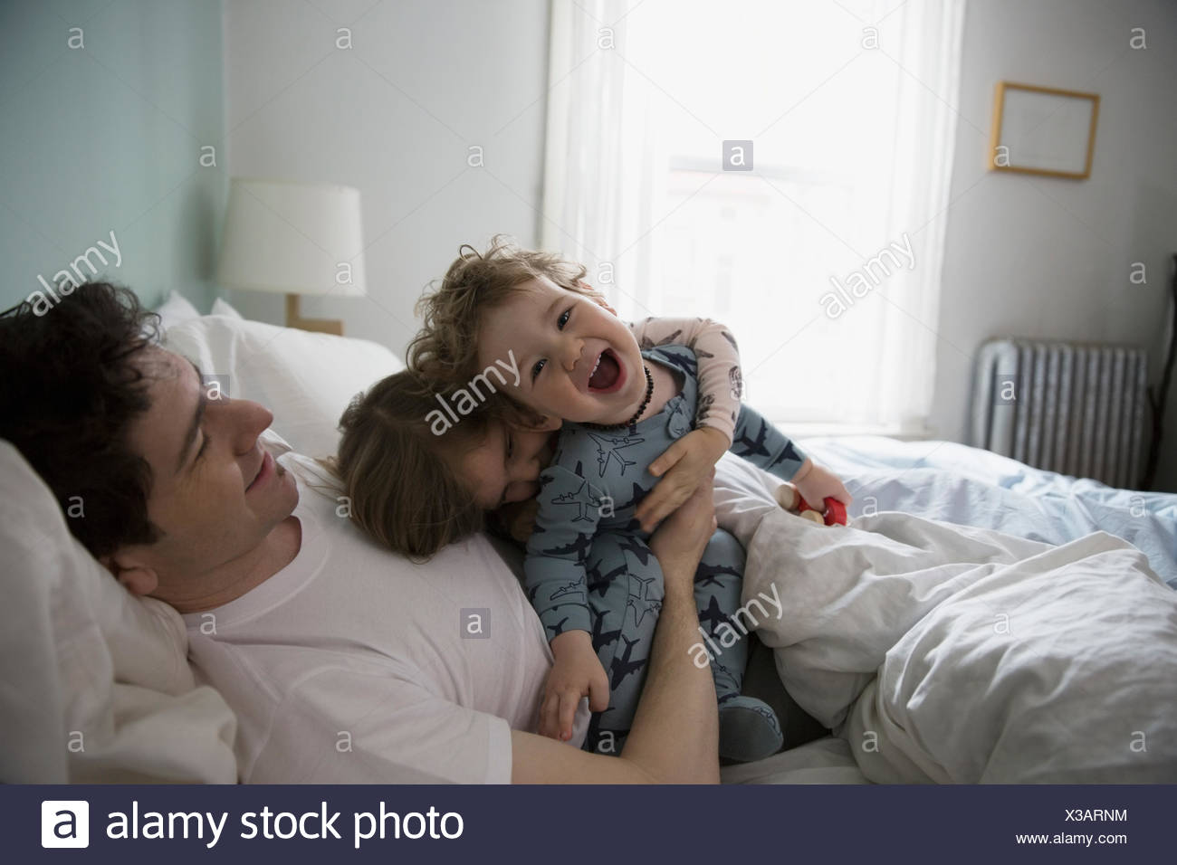 Father and children in pajamas playing in bed - Stock Image