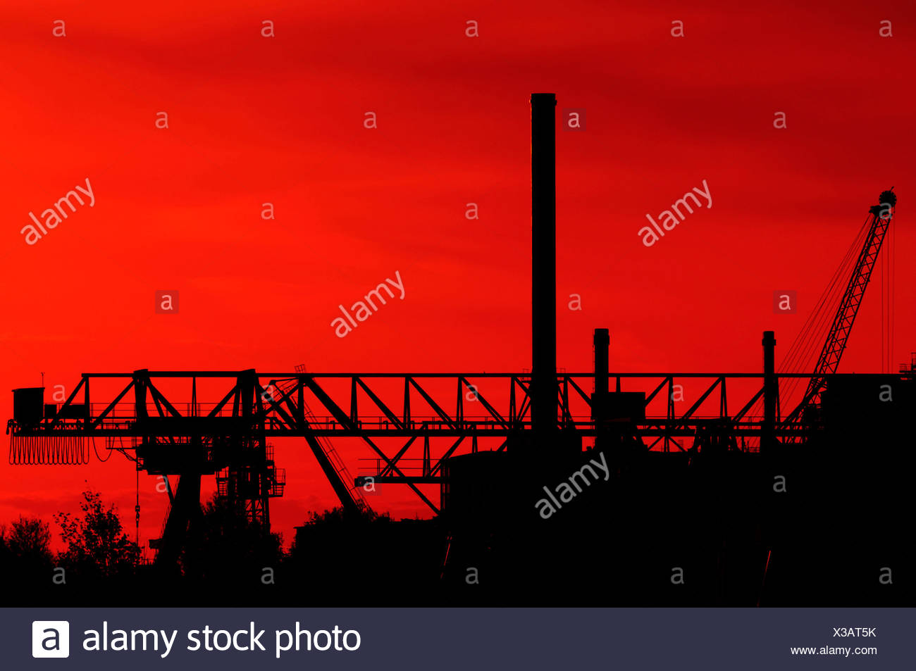 Cranes silhouetted at an industrial plant, Duesseldorf, North Rhine-Westphalia, Germany - Stock Image