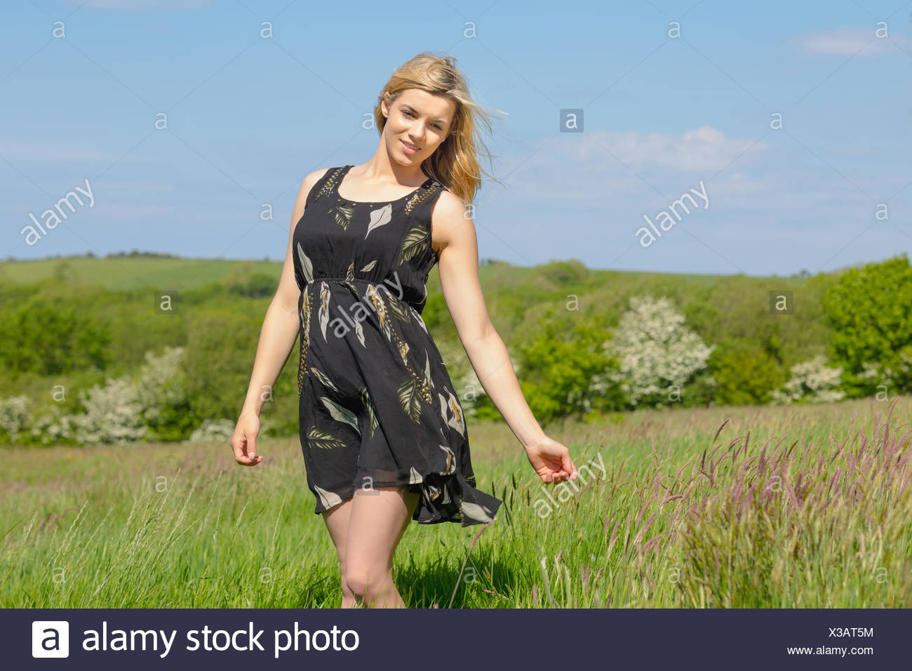 Pretty blonde in sundress smiling at camera - Stock Image