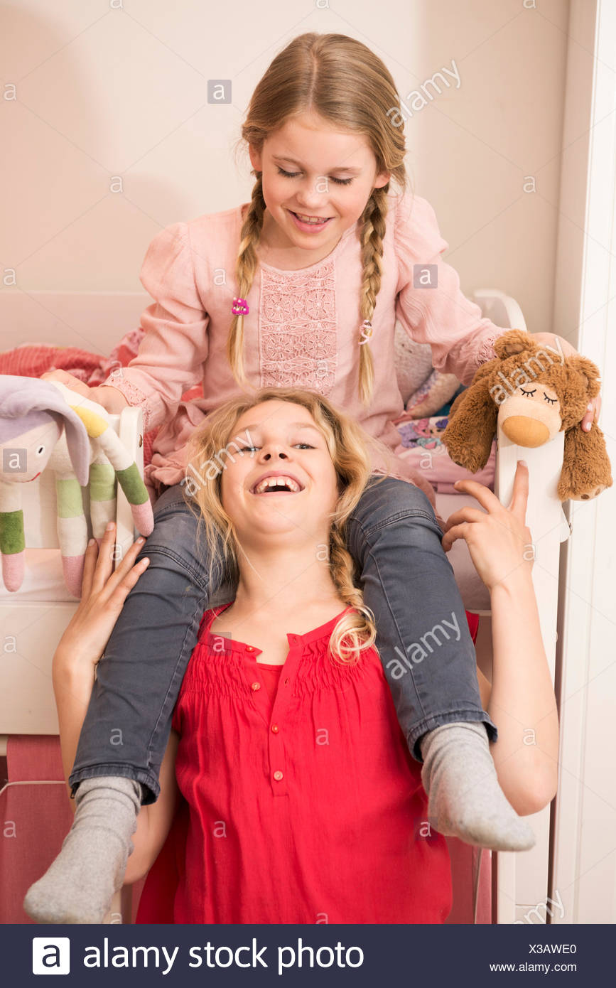 Girl laughing whilst giving sister a shoulder ride in bedroom - Stock Image