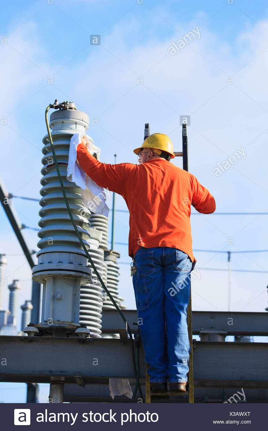 Power engineer cleaning a fluid filled high voltage insulator, Braintree, Massachusetts, USA - Stock Image