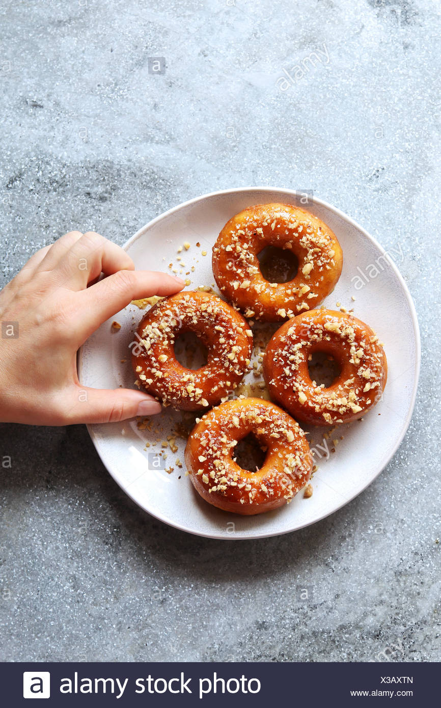 Female hand grabbing a donut with honey maple syrup and ground walnuts from a plate.Top view - Stock Image