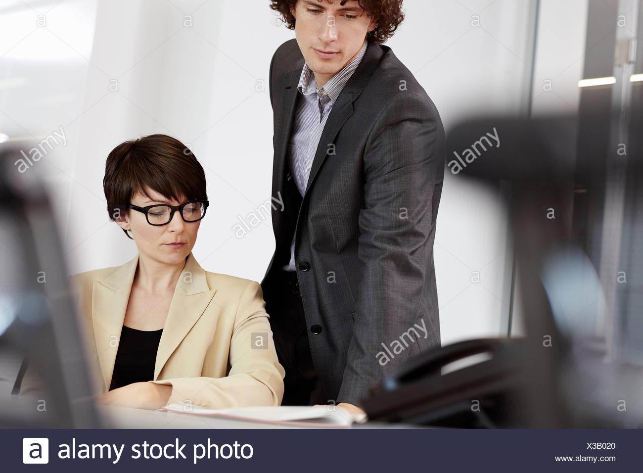 Businesswoman sitting at desk, man looking over her shoulder at paperwork - Stock Image