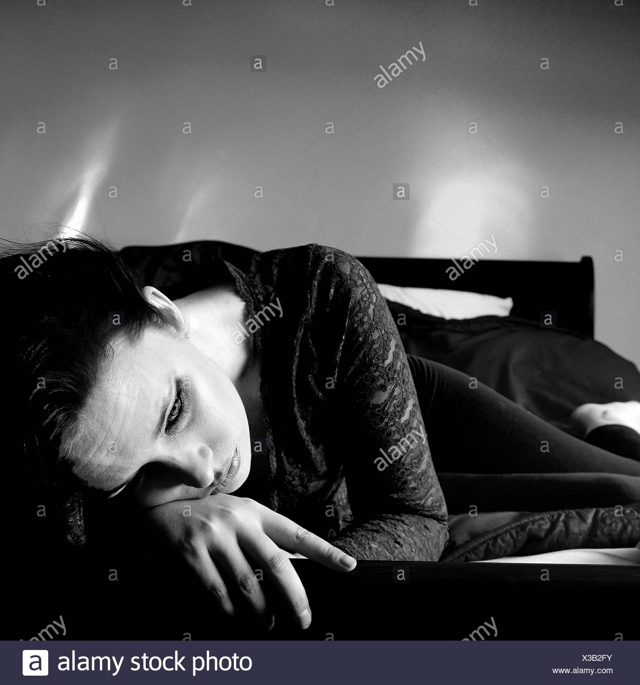 High Angle View Of Sad Woman Relaxing On Bed At Home - Stock Image