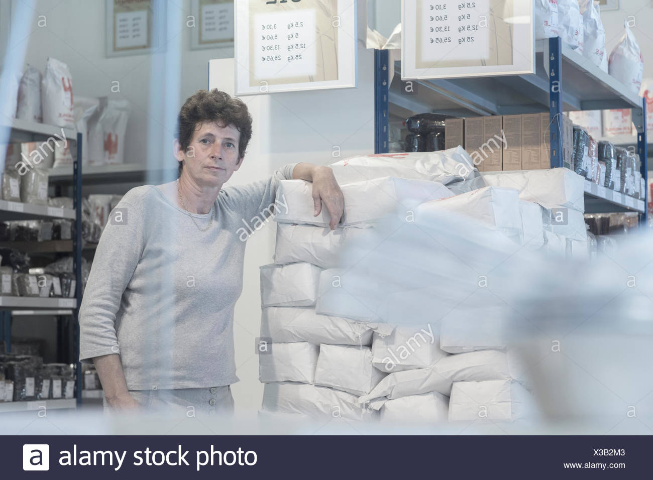 Portrait of female miller and flour sacks in wheat mill stockroom - Stock Image