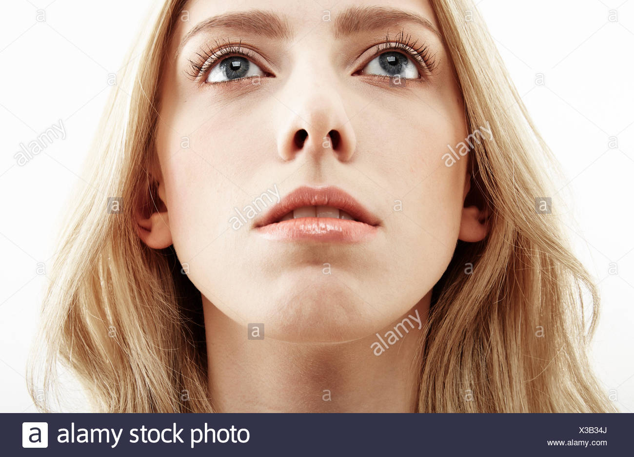 Cropped close up studio portrait of young woman gazing upward - Stock Image