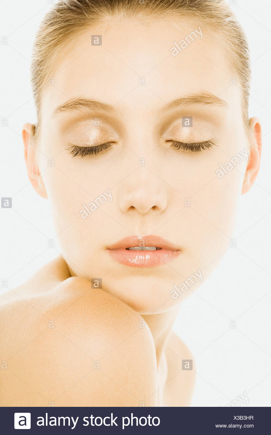 Woman with eyes closed, wearing natural cosmetics, resting chin on shoulder - Stock Image