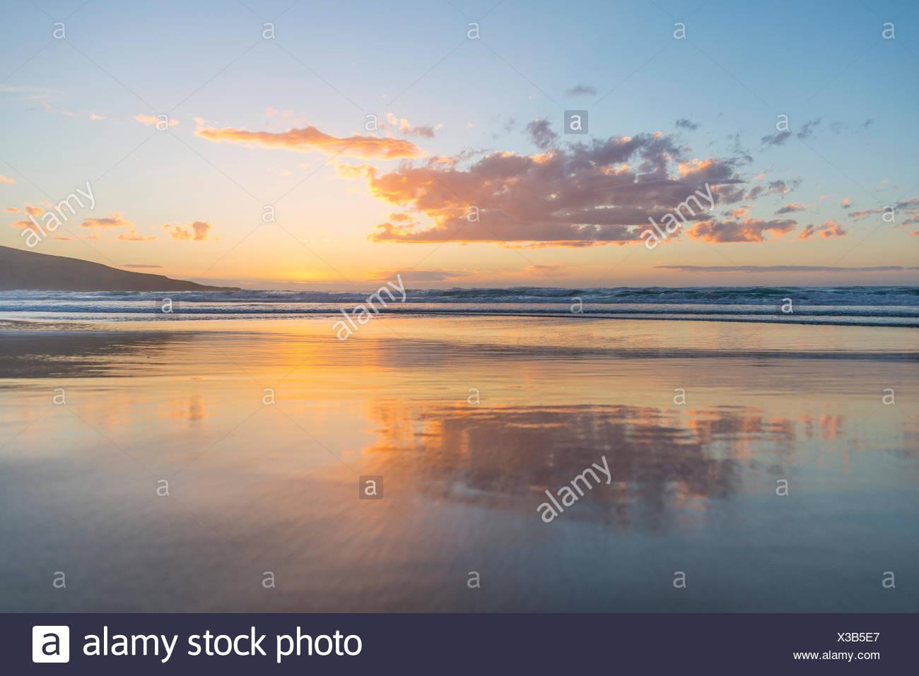 Reflection, sunset over the sea, Sandfly Bay, Dunedin, Otago, South Island, New Zealand - Stock Image
