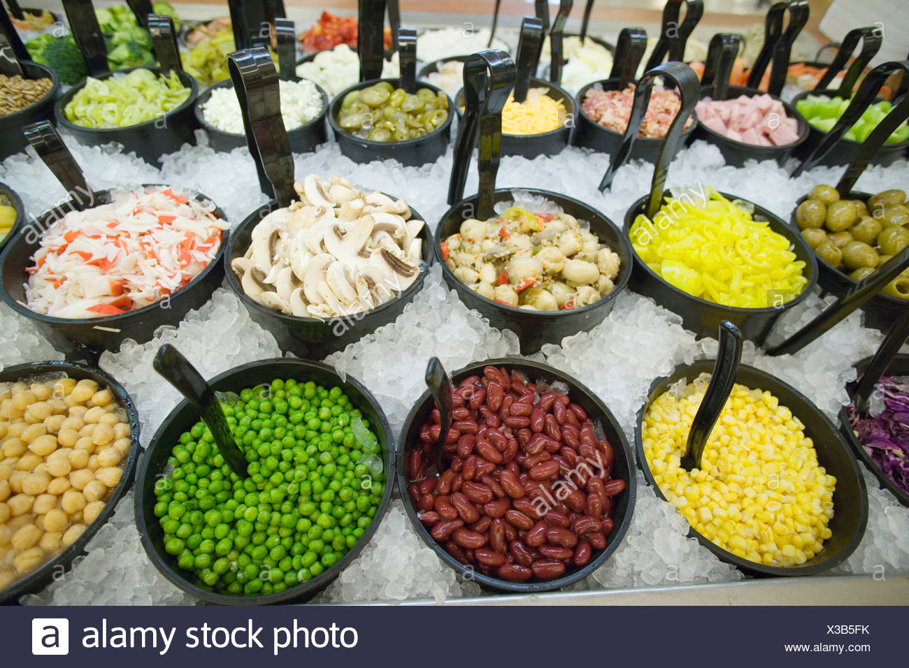 Selection of fresh food in bowls chilled with ice in supermarket still life - Stock Image