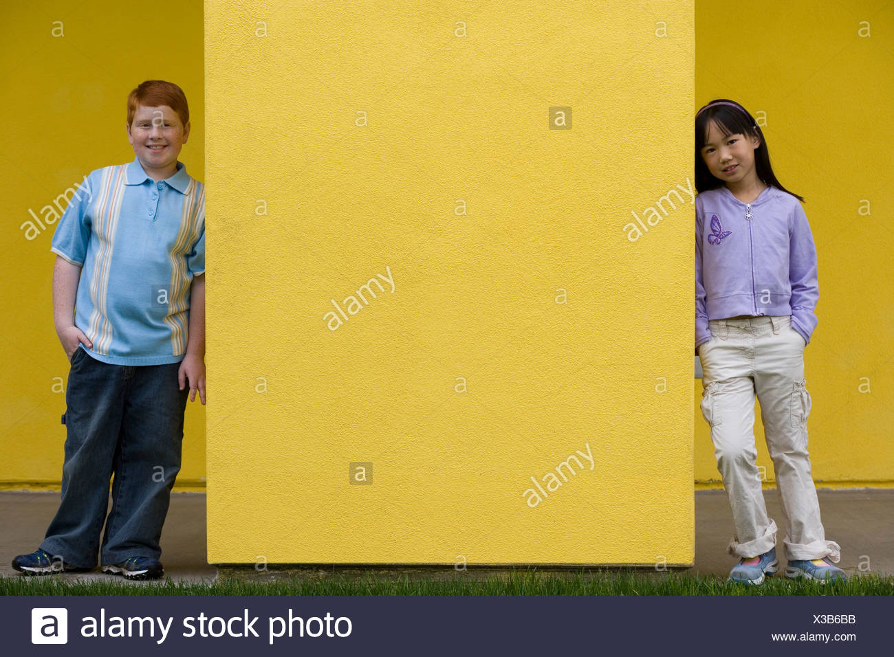 Boy 10 12 and girl 9 11 standing at opposite ends of yellow wall smiling front view portrait - Stock Image
