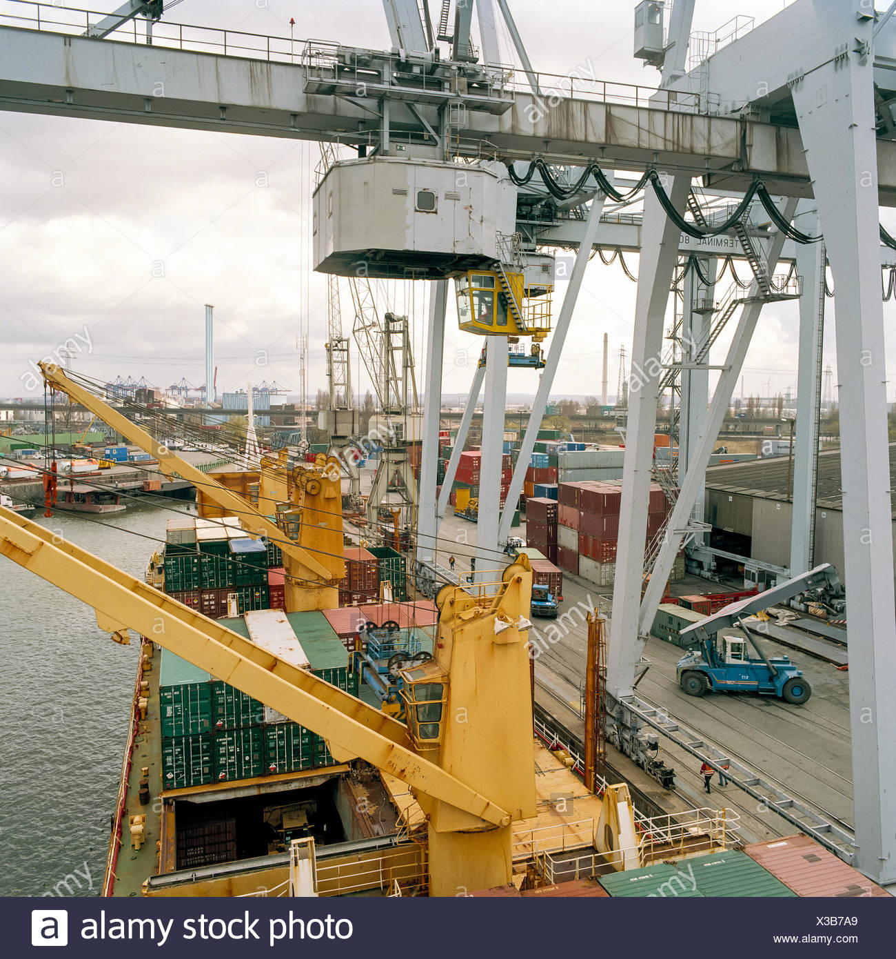 Gantry crane and containers on ship in port - Stock Image