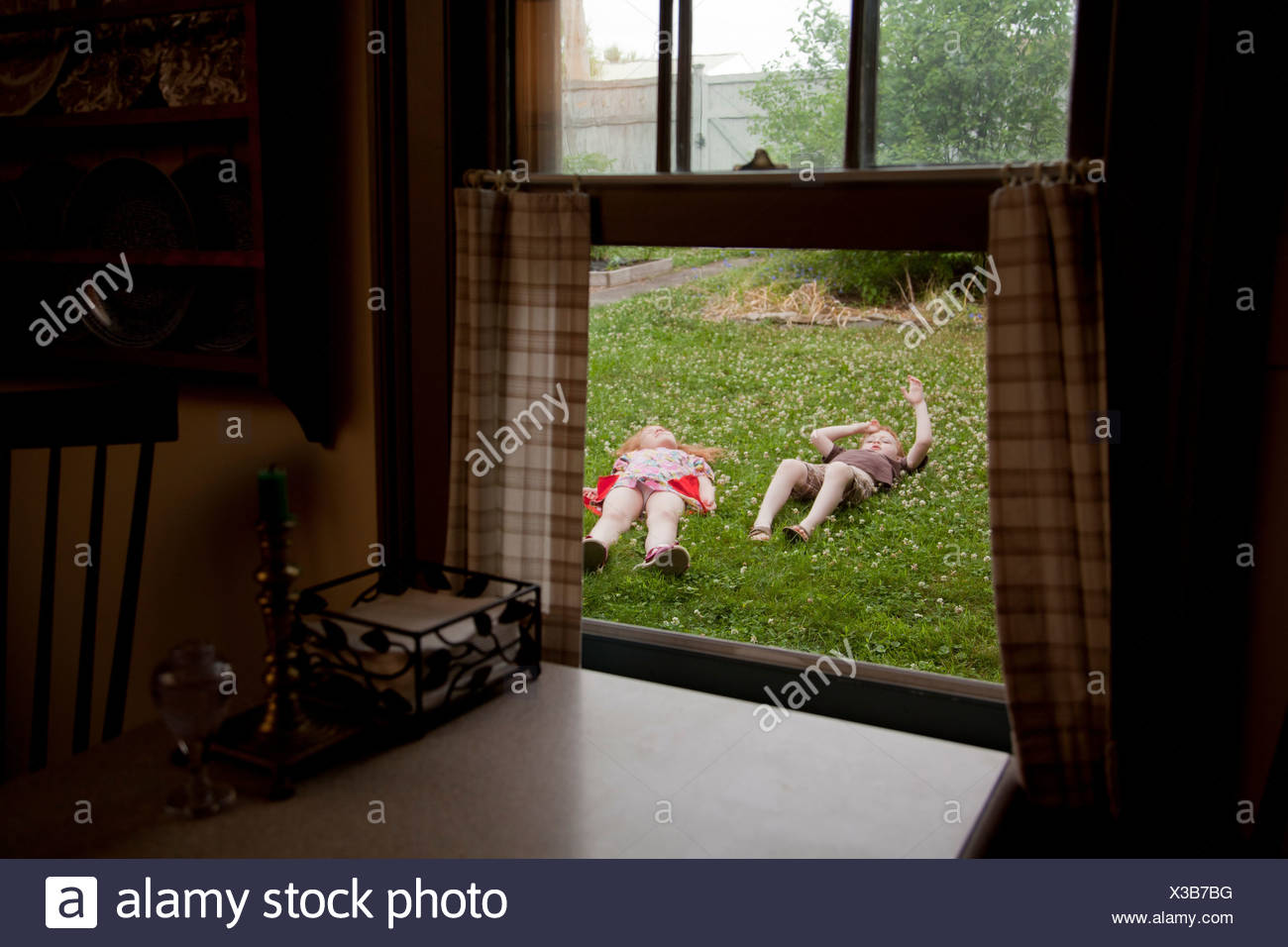 View through window of boy and and girl lying in garden - Stock Image
