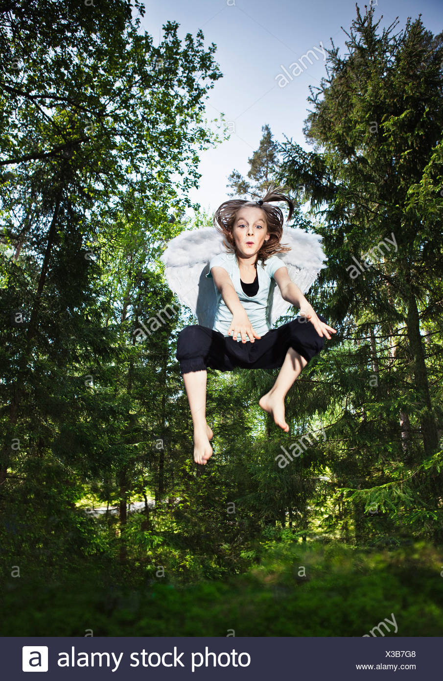 Girl wearing wings and jumping in forest - Stock Image