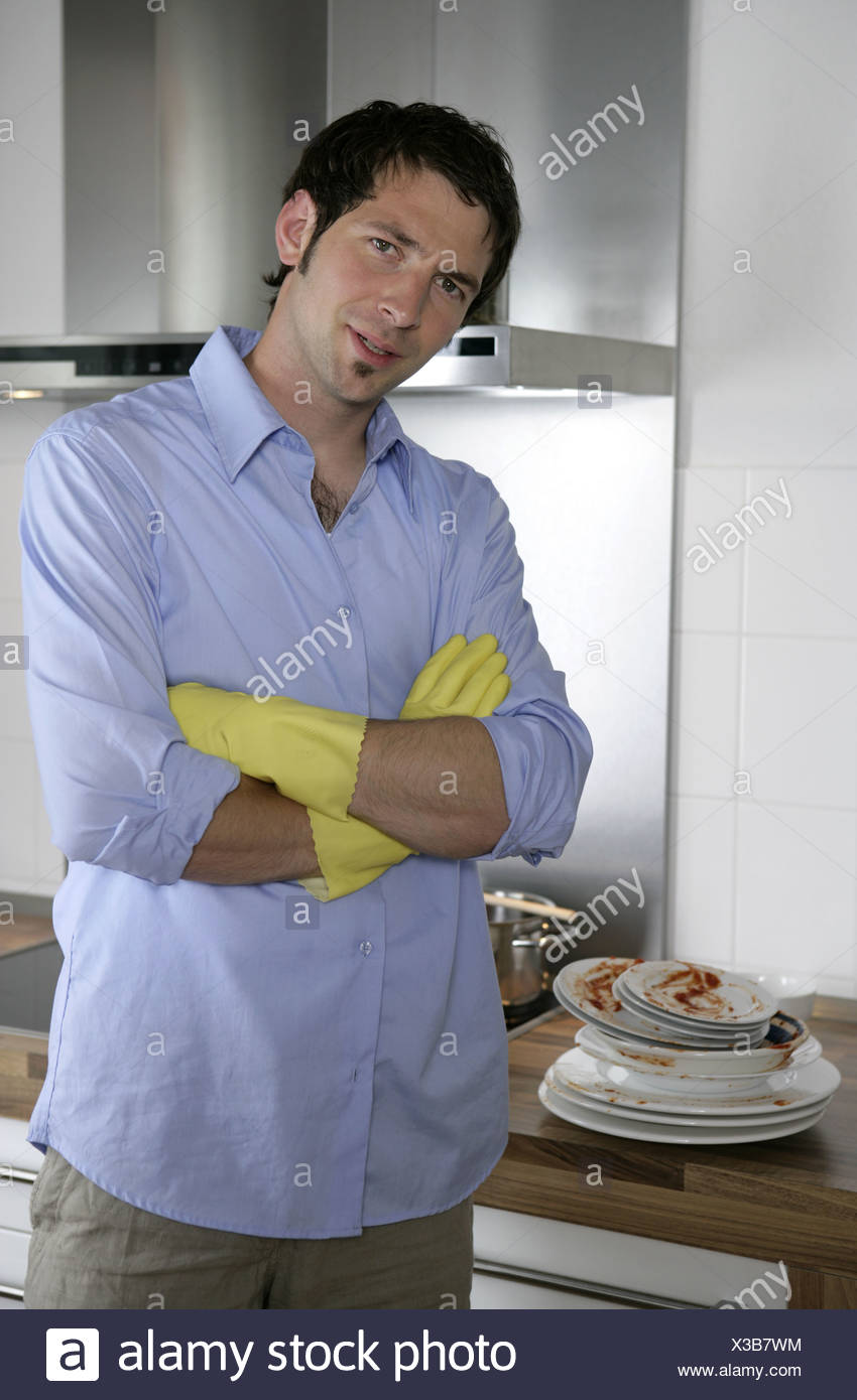 Young man with rubber gloves in kitchen portrait Stock Photo