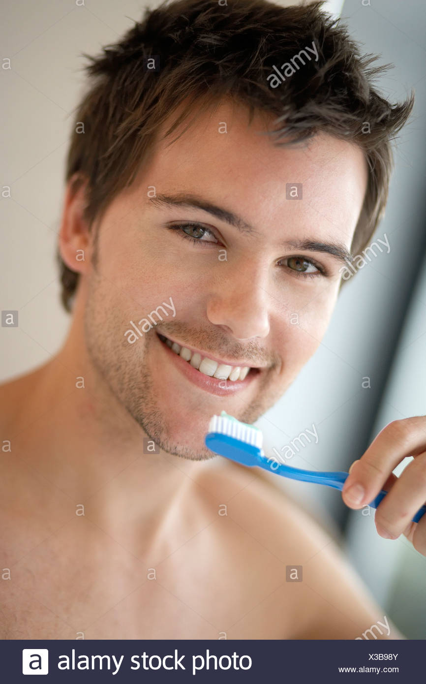 Young man brushing his teeth, close-up - Stock Image