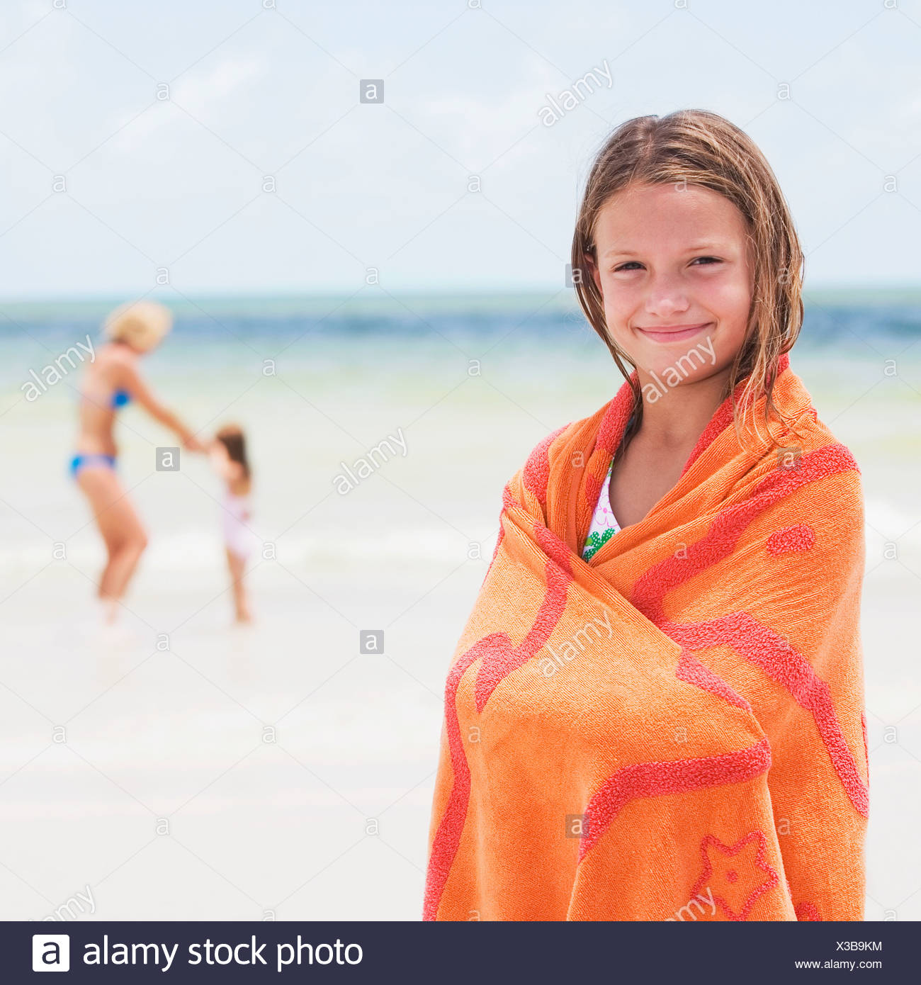 Girl wrapped in towel on beach Stock Photo