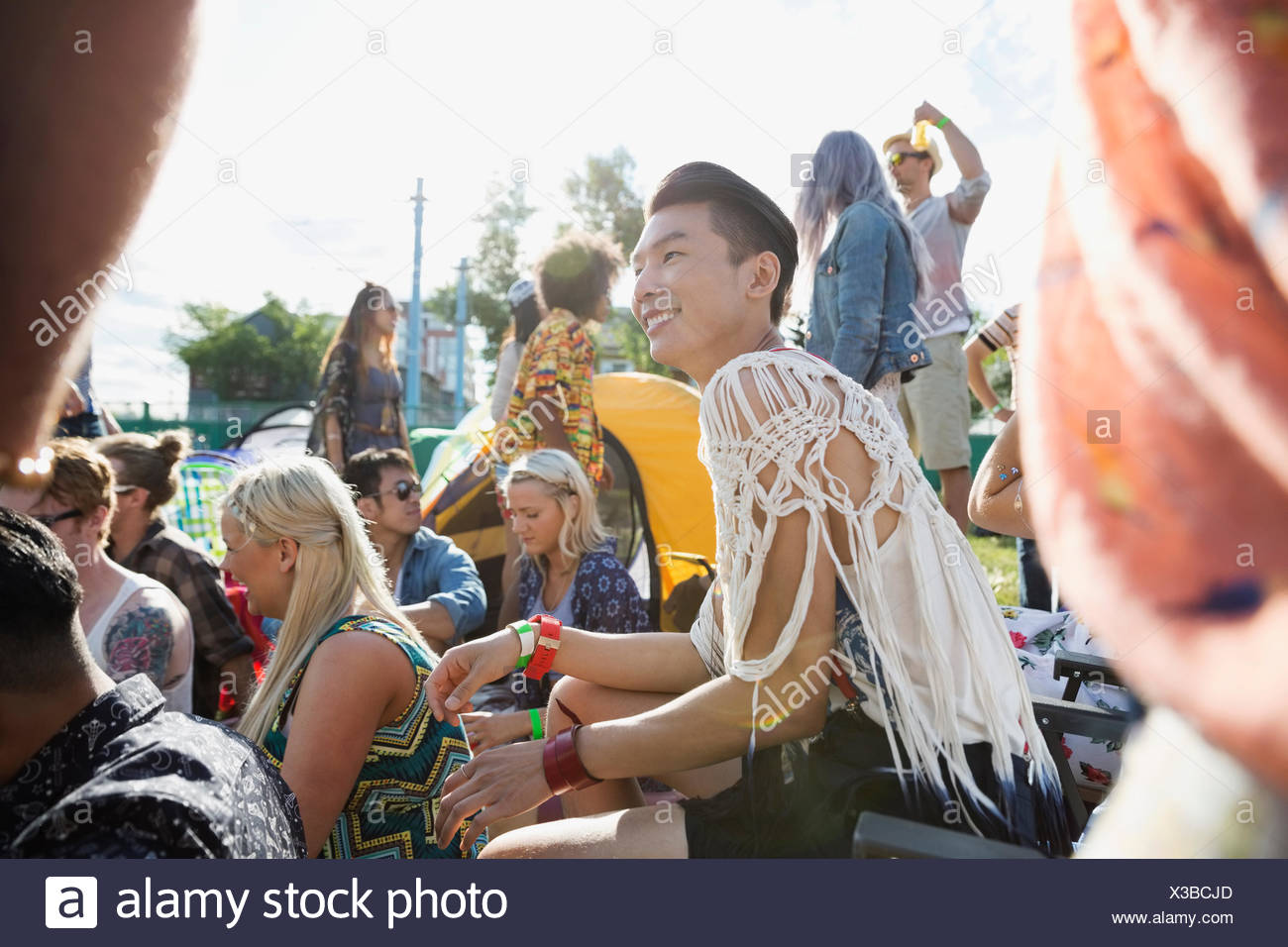 Smiling young man enjoying summer music festival - Stock Image