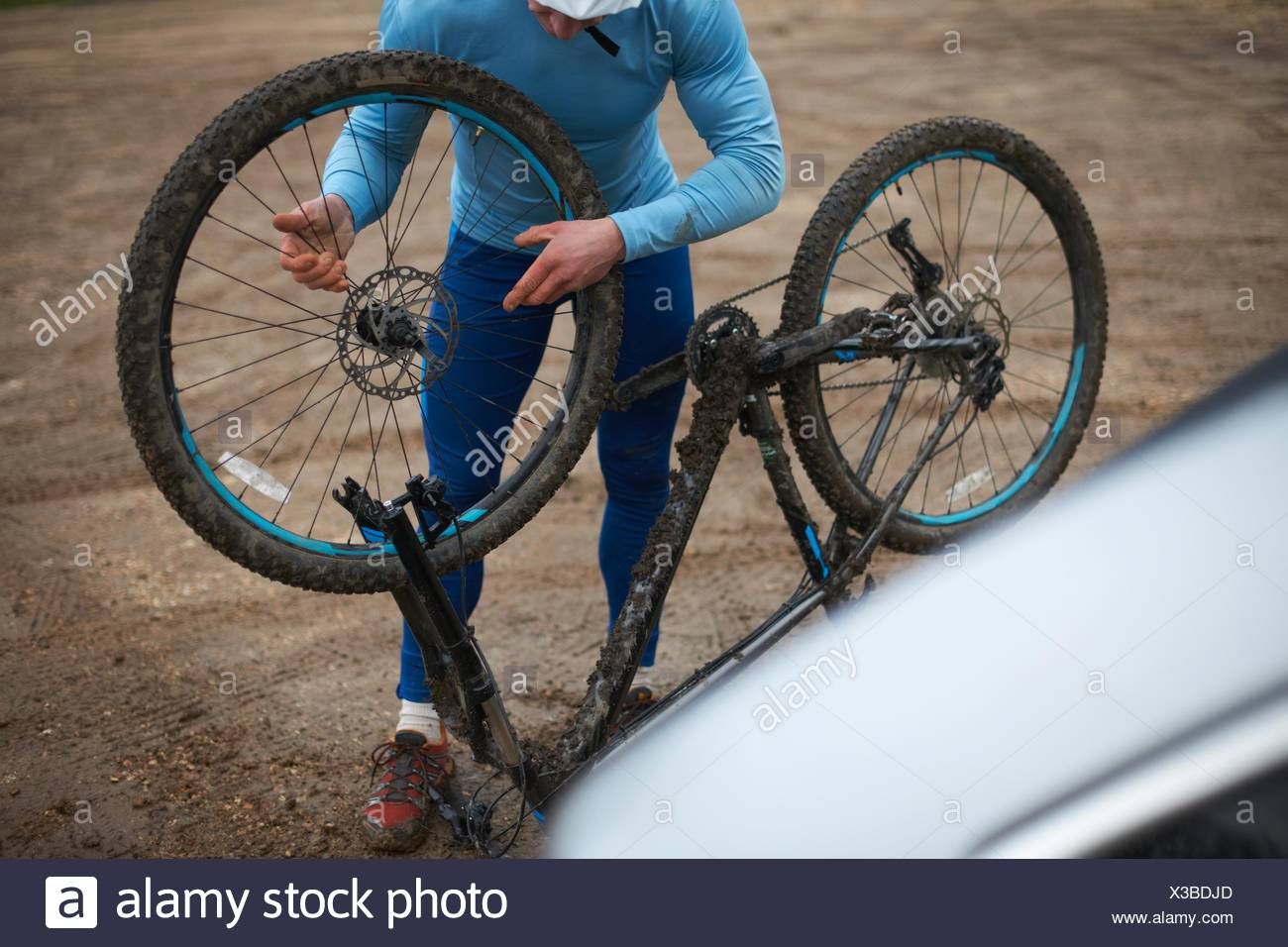 Cyclist fitting bicycle wheel to upside down bicycle - Stock Image
