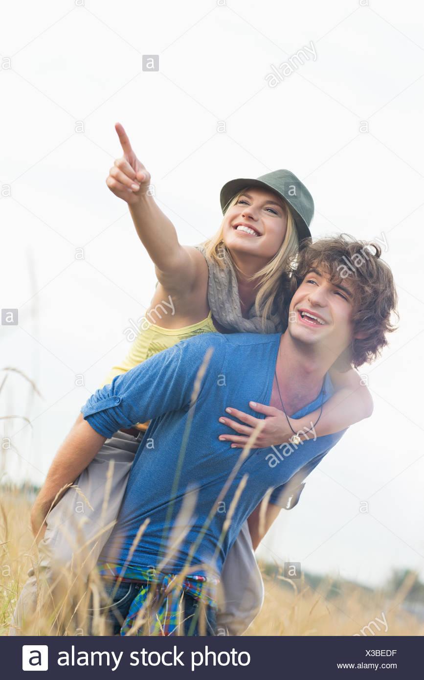 Cheerful woman showing something while enjoying piggyback ride on man in field Stock Photo