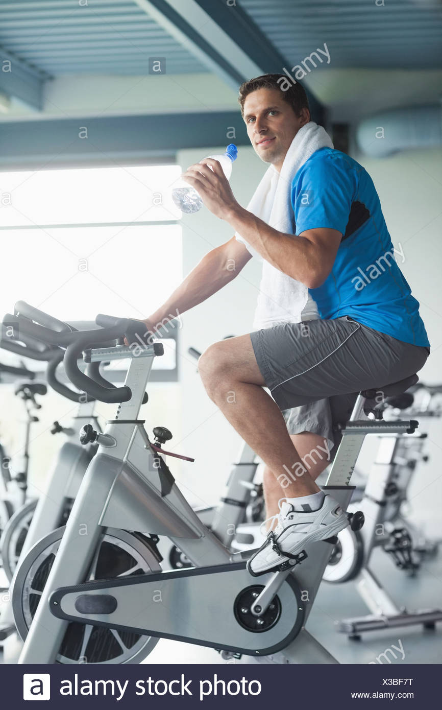 Tired man with water bottle working out at spinning class - Stock Image