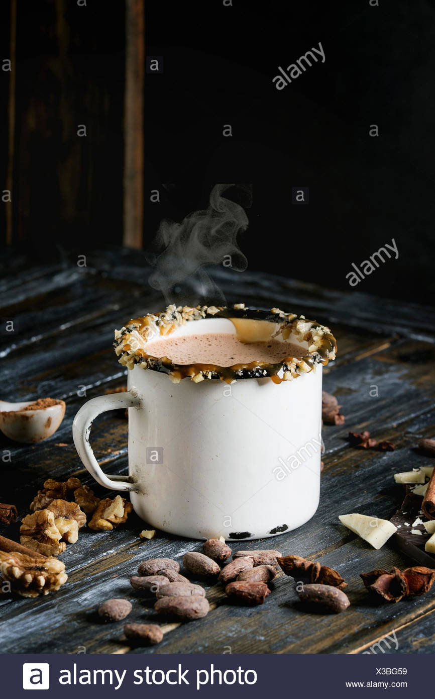 Vintage mug of hot chocolate, decor with nuts, caramel, spices. Ingredients above. Chopped dark and white chocolate, cocoa beans, anise over old woode Stock Photo