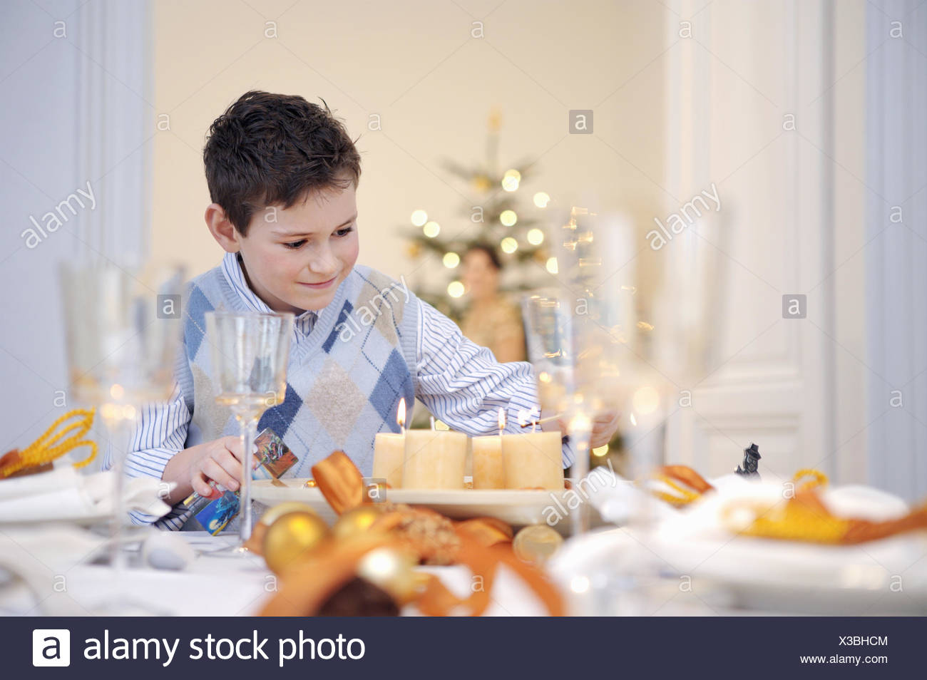 Boy helping set table at Christmastime - Stock Image