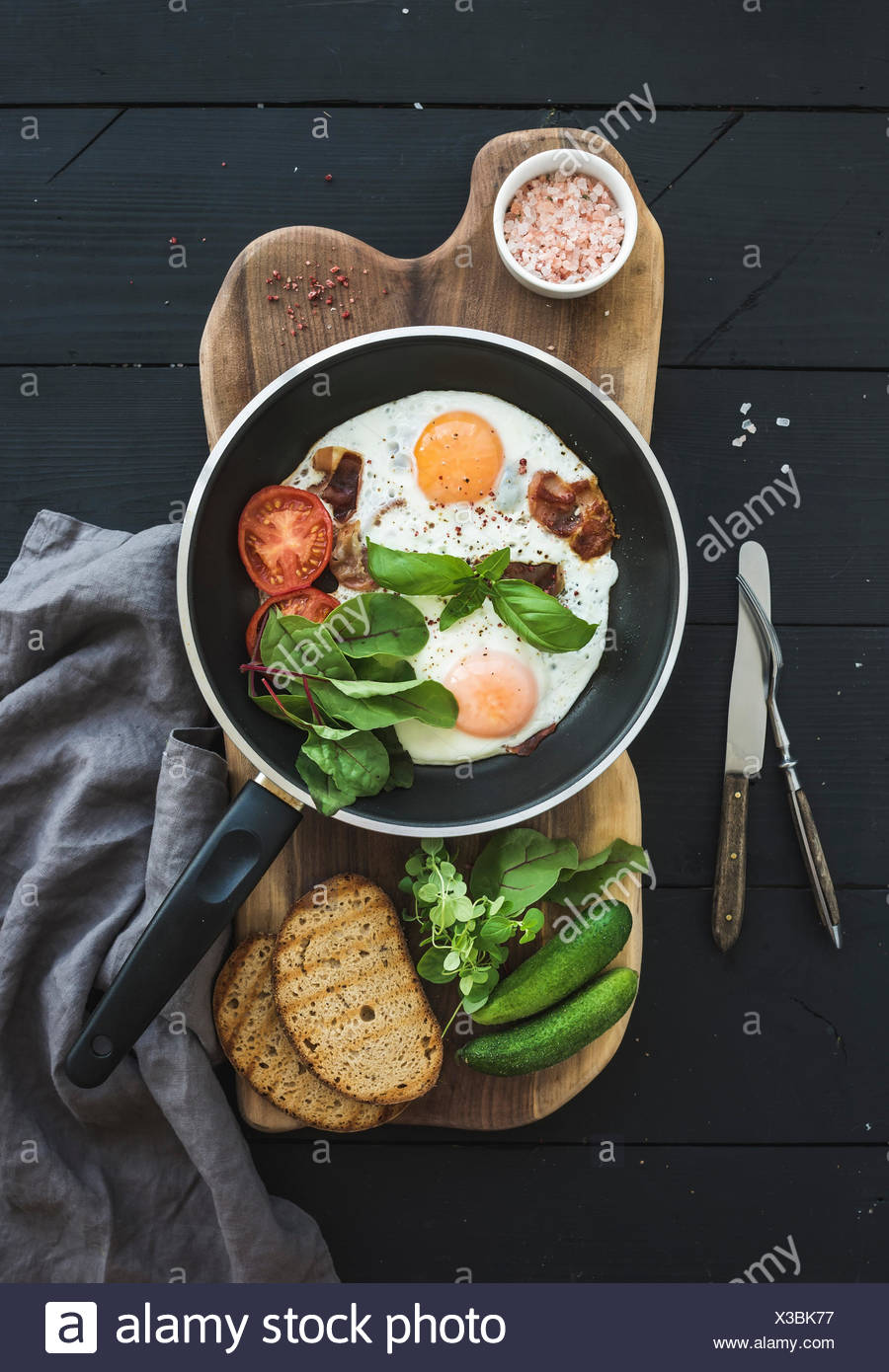 Pan of fried eggs, bacon, cherry tomatoes and fresh herbs with bread on wooden board over dark wooden background, top view - Stock Image