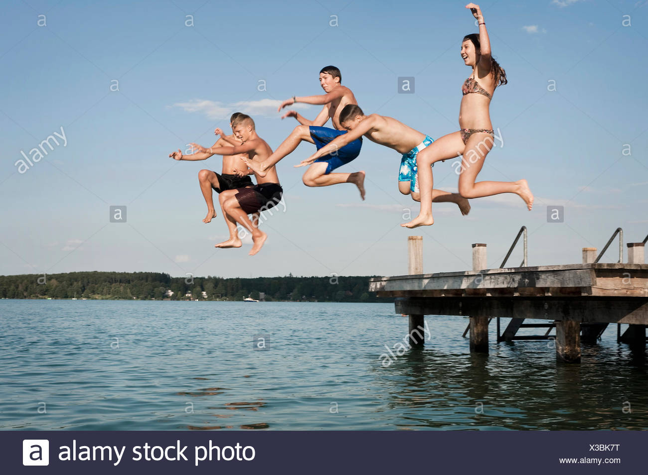 Five teenagers jumping from a jetty into lake - Stock Image