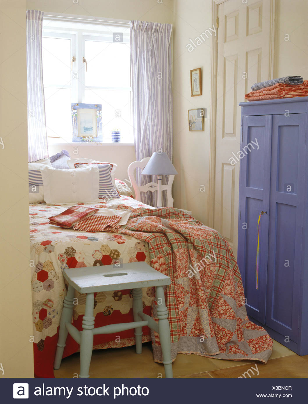 Charmant Painted Stool Below Bed With Patchwork Quilt And Floral Throw In Small  Bedroom With Painted Blue Wardrobe