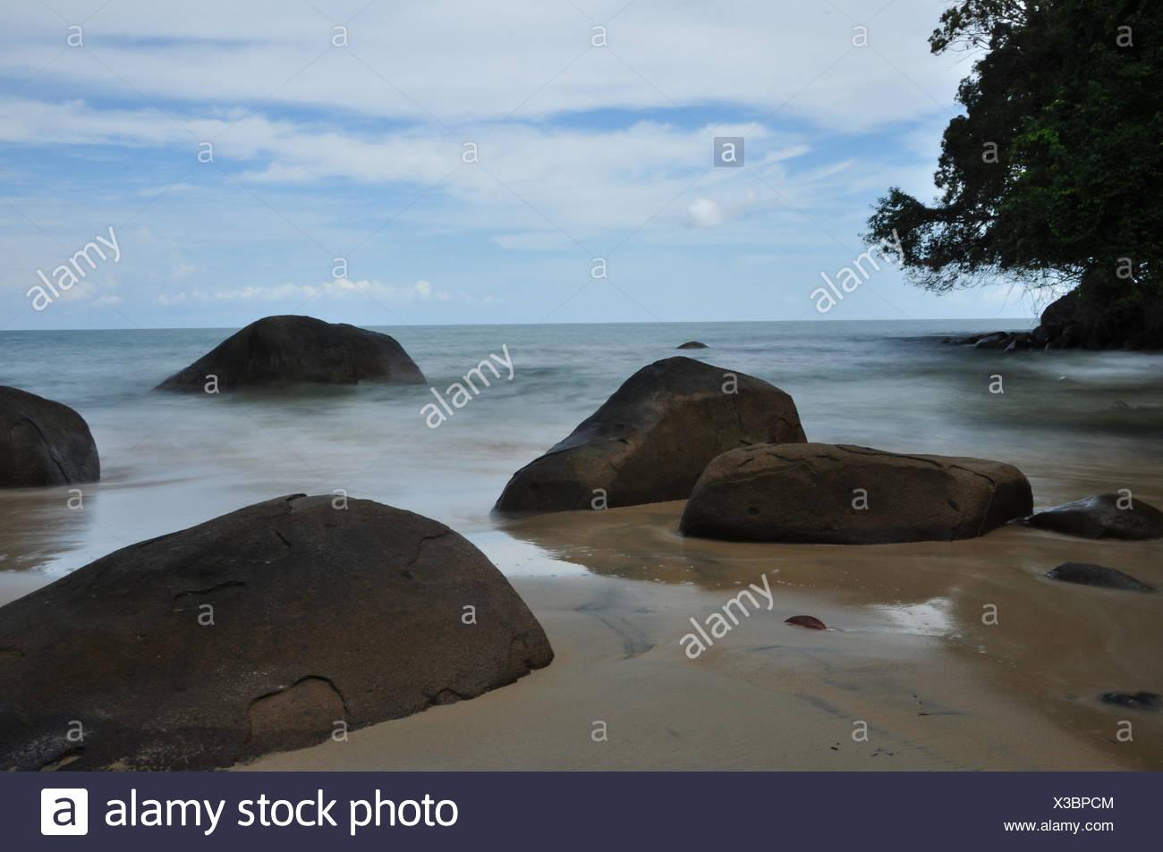 stones at small sandy beach - Stock Image